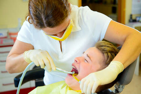 teenager is treated by female dentist in dental surgery Stock Photo