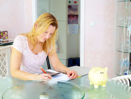 calculate: blond woman calculate housekeeping allowance in living room