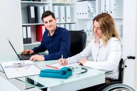 paraplegico: disabled businesswoman in wheelchair and her colleague in the office Foto de archivo