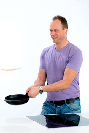 young man cooking pancake in the kitchen Stock Photo