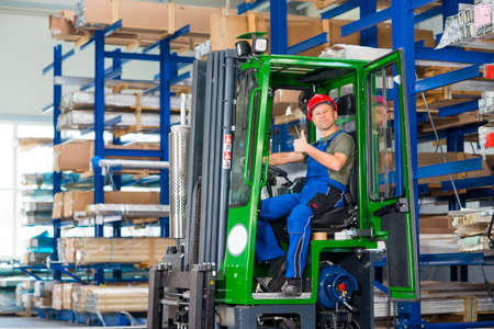 un trabajador de cada fábrica en la carretilla elevadora con el pulgar arriba Foto de archivo