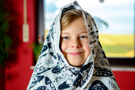 jubilating: funny girl with blanket on head is smiling