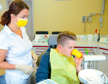 A teenager at a female dentists surgery