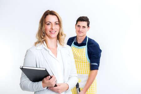 joven y bella mujer de negocios y su marido con el aspirador en el fondo