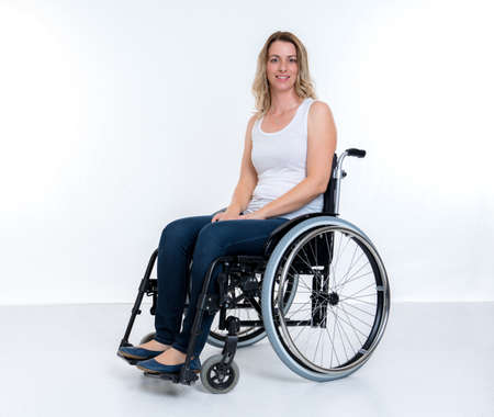 young disabled woman in wheelchair infront of white background Stock Photo