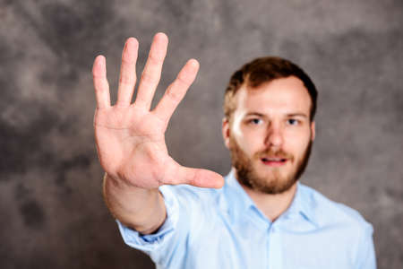 young bearded man looking angry and showing open hand