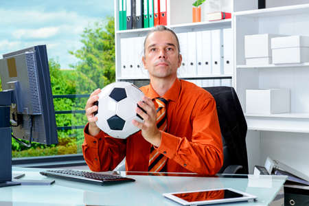 young business man at his desk with soccer ball  Stock Photo