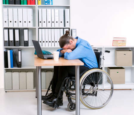 downcast: disabled business man in wheelchair is depressed  Stock Photo