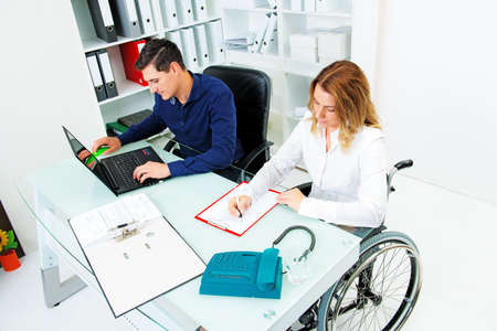 disabled businesswoman in wheelchair and her colleague in the office Stock Photo