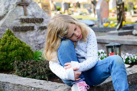 little sad girl in front of grave Standard-Bild