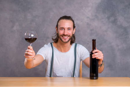 skoal: young man sitting at the table and drinking red wine Stock Photo