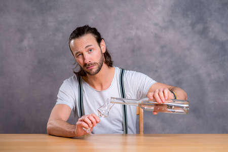 skoal: young man in front of gray background drinking clear spirit