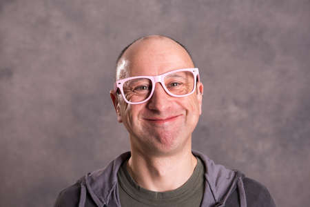funny baldheaded man with pink glasses in front of gray background