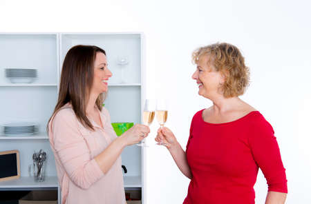young woman and her mother cooking together and drinking sparkling wine