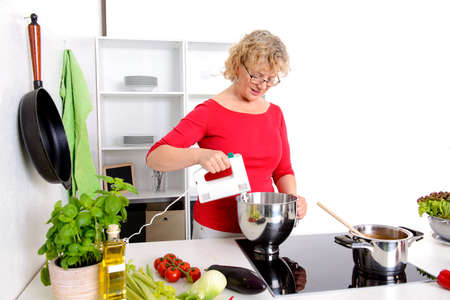 blond woman cooking and baking in a white kitchen Stock Photo
