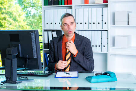 young business man behind his desk in summerly hot office