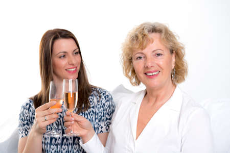 skoal: young woman and her mother drinking champagne  in front of white background