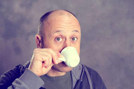 calvicie: Café de consumición del hombre calvo delante de fondo gris