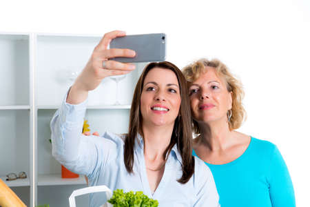 self testing: young woman and her mothertaking a selfie together in the kitchen