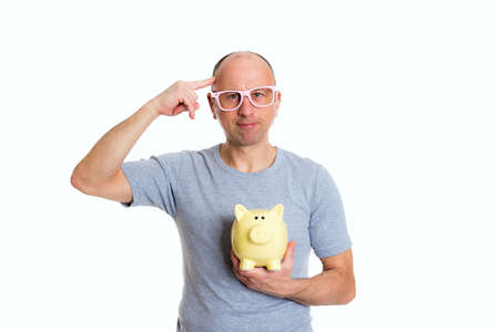 young man in gray shirt with pink glasses and piggybank show a bird