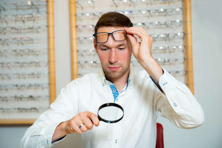 in optician shop- young man with magnifier selecting new reading glasses