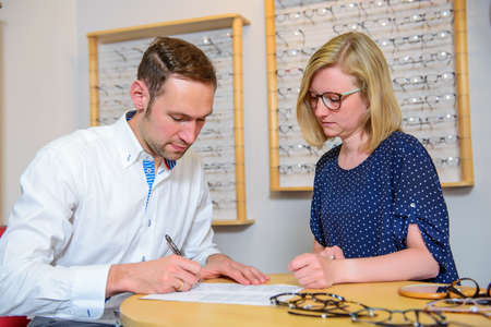 autograph: in optician shop- young woman and man selecting new glasses Stock Photo