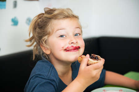 marmelade: funny girl eating bread roll with dark marmelade Stock Photo
