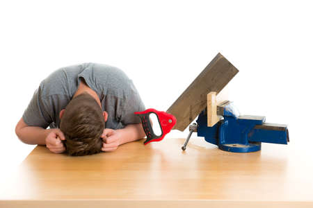 listless teenager in professional training using hand saw
