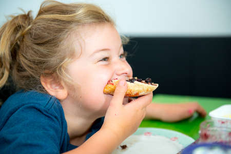 funny girl eating bread roll with dark marmelade Stock Photo
