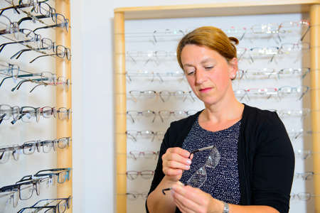 in optician shop- dark haired woman selecting new glasses Stock Photo