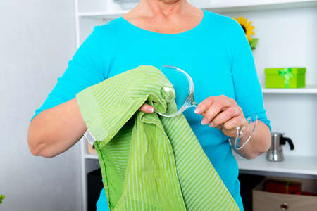 woman standing in the kitchen and dry off a wine glass