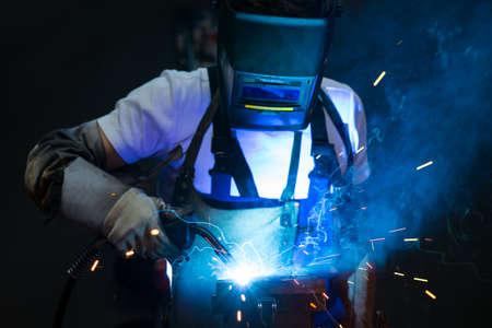 man lassen van metaal in de fabriek