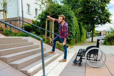 young man standing with wheelchair in front of stairs