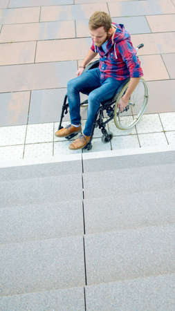 young disabled man in wheelchair in front of stairs from above