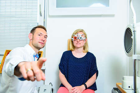 young optician checking eyes of woman for new glasses