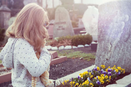 little sad girl in front of grave Stock fotó