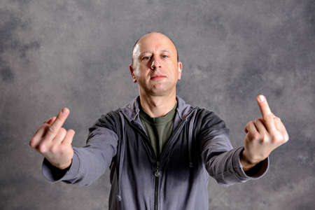 young baldheaded man in front of gray background showing middle finger