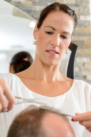female hairdresser cutting hair of man in her shop