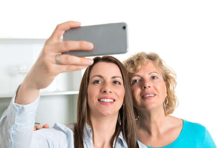 self testing: young woman and her mother taking a selfie together in the kitchen