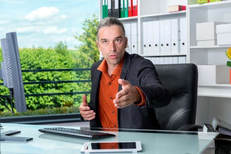 young business man behind his desk greeted a client Reklamní fotografie