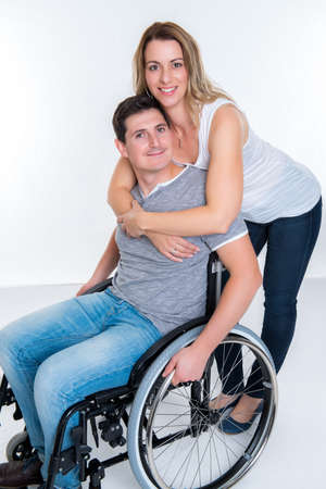 Young disabled man in wheelchair and his wife