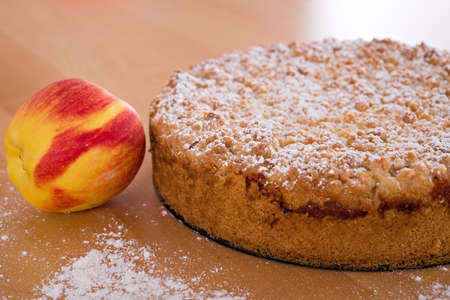 round apple pie with crumbles on wooden ground