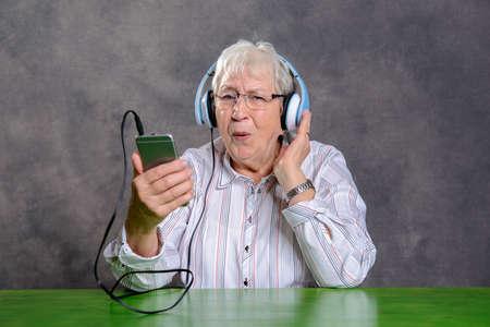 tact: gray hairy elderly woman listening music with headphone Stock Photo