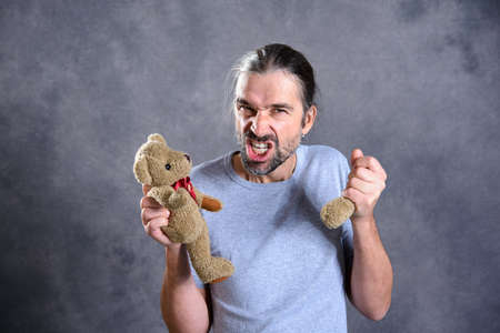 young man with broken teddy bear looking bad Stock Photo