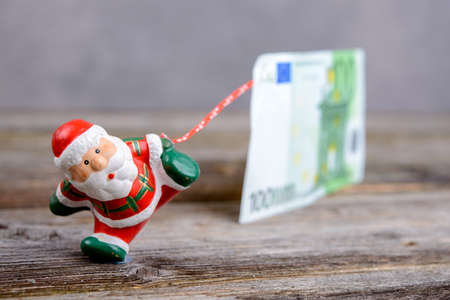 Little Santa Claus pulling big euro banknote Stock Photo