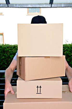 Überforderter Postbote mit Paketen und dunkler Kappe