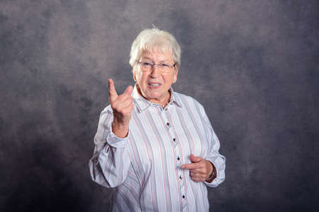 Gray hairy elderly woman looking angry and showing forefinger