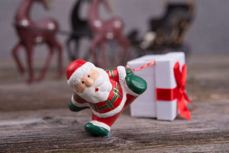 little Santa Claus pulling white gift box Stock Photo