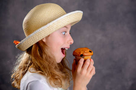 nice girl with blond hair in white dress and straw hat eating muffin Stock Photo