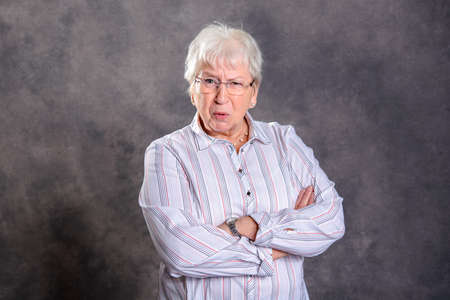 gray hairy elderly woman with crossed arms looking angry in front of gray background
